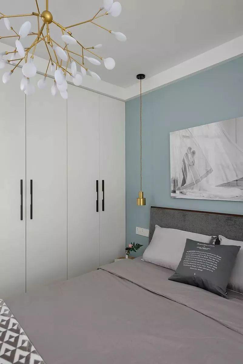 卧室的墙面以淡蓝色为主,搭配暖灰色的床单,咖色的窗帘,黑白灰的